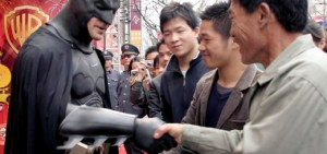 "FILE - In this March 26, 2006 file photo, an actor clad in a Batman costume greets local spectators after the grand opening ceremony of the Warner Bros. Studio Store in Shanghai, China. Hollywood studio Legendary Entertainment which produced ""The Dark Knight"" from 2008 signed an agreement with the state-owned China Film Group on Thursday, May 30, 2013 in Beijing. (AP Photo/Eugene Hoshiko, File)"